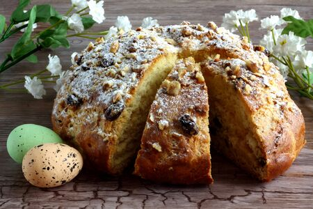 Sweet braided homemade sliced bread with easter eggs and white florets with leaves decorated on wooden desk - table - easter time