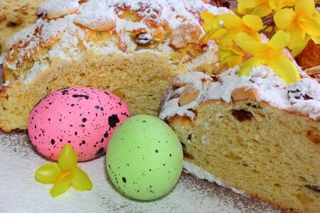 Traditional sweet braided homemade sliced easter bread with easter eggs and yellow florets - golden rain flower decorated on wooden desk - table - easter time