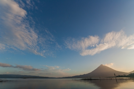 Volcano Arenal in the early morning with reflection in the water. photo