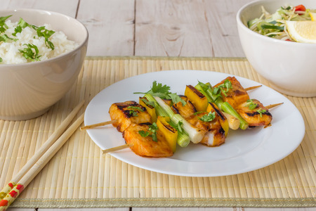 Asian tilapia filet on a skewer, served with rice, salad and lemon photo