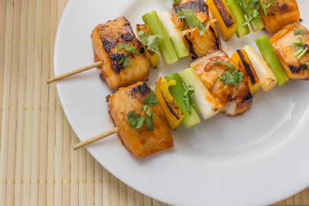 Asian tilapia filet on a skewer, served on a white plate photo