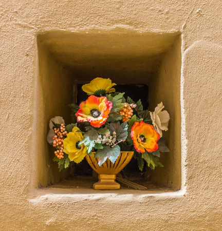 yeloow: Yeloow wall niche with a pot of flowers in Italy Stock Photo