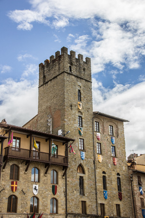 Tower with flags and shields at the Piazza Grande of Arezzo, Italy