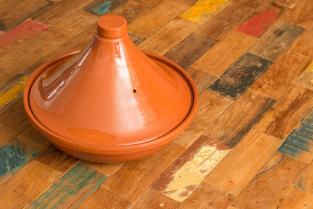 moroccan cuisine: Moroccan brown tagine on a colorful table