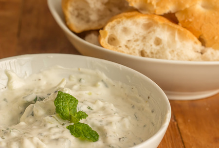 moroccan cuisine: Yogurt, mint and lemon sauce with white bread on a wooden table