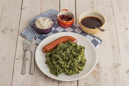 smoked sausage: Boerenkool with smoked sausage and bacon on a white plate Stock Photo