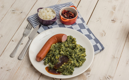 smoked sausage: Boerenkool with smoked sausage, bacon, pickled onions and gravy on a white plate