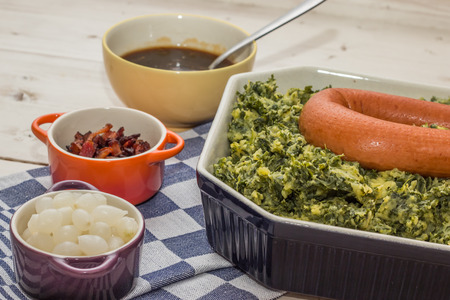 Typical dutch dish boerenkool with kale, mashed potatoes, sausage, bacon and pickled onions