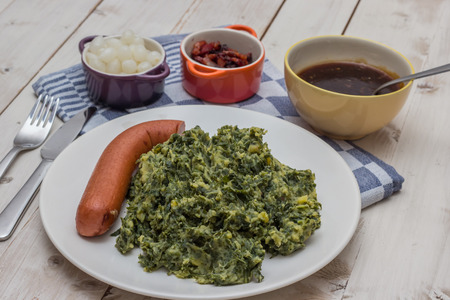 Boerenkool with smoked sausage, bacon and gravy on a white plate Imagens