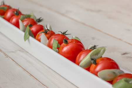 elongated: White elongated dish filled with cherry tomatoes, spring onions and pepper