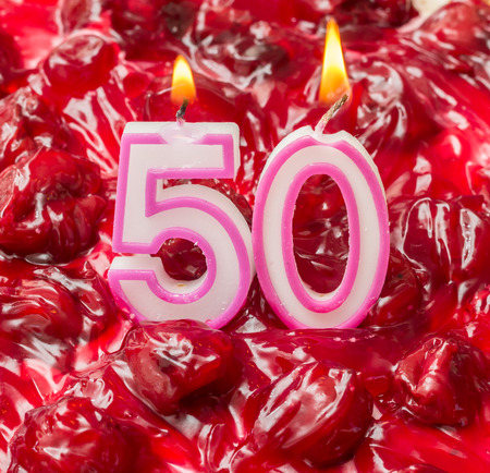 50th: Cherry cheese cake with burning candles for 50th birthday