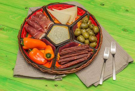 tapas espa�olas: Cesta con tapas espa�olas en una mesa de madera verde r�stico Foto de archivo