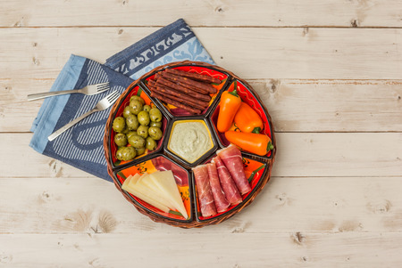 spanish tapas: Basket with Spanish tapas on a rustic white wooden table