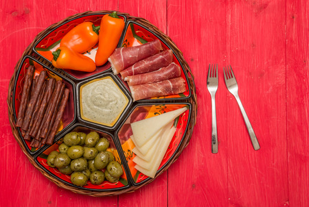 cured ham: Basket with Spanish tapas, manchego, cured ham, olives, peppers and chorizo