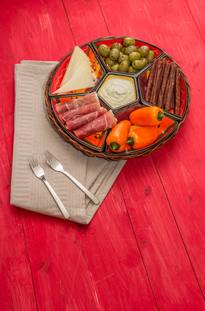 spanish tapas: Basket with Spanish tapas on a rustic red wooden table
