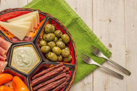 tapas españolas: Cesta con tapas españolas en una mesa de madera blanca rústica