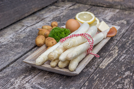 white asparagus: White asparagus with potatoes and parsley on a rustic wooden plate Stock Photo