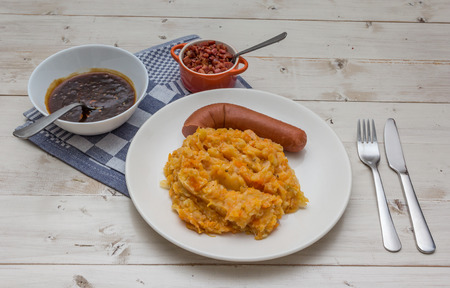smoked sausage: Hutspot with smoked sausage and bacon on a white plate Stock Photo