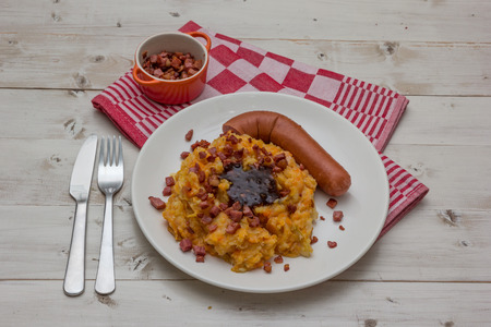 smoked sausage: Hutspot with smoked sausage, gravy and bacon on a white plate
