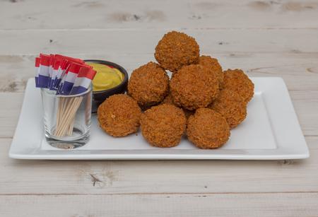Nederlandse snack bitterballen met weinig nederlandse vlaggen op een witte plaat Stockfoto