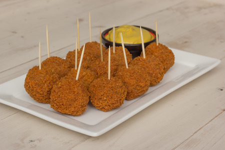 picks: Dutch snack bitterballen with mustard and cocktail picks on a white plate