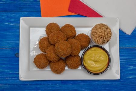 Hollandse snack bitterballen met mosterd op een witte plaat