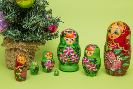 matriosca: Russian wooden dolls around a Christmas tree on a green background