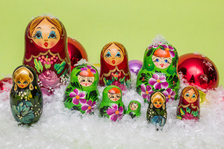 matriosca: Russian wooden dolls with snow and Christmas balls on a green background