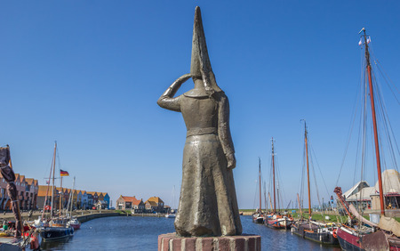 Statue of a lady looking out over sea in Stavoren, Netherlands Editorial