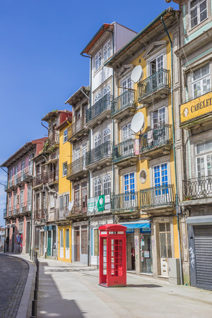 cabina telefonica: Classic red phone booth and colorful houses in Porto, Portugal