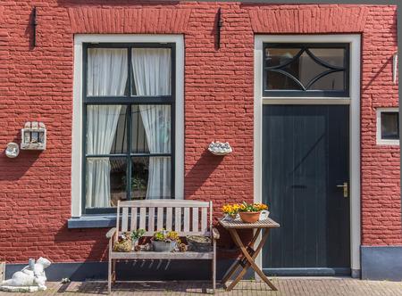 casa roja con un banco delante de él Foto de archivo