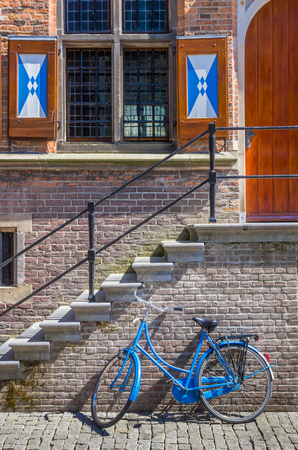 dutch typical: Blue bicycle in front of typical dutch building with blinds