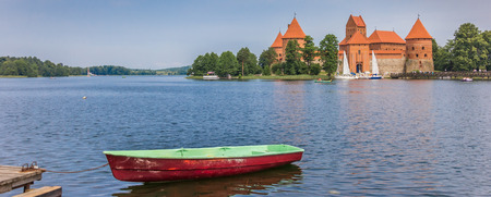 green boat: Panorama of Trakai castle and a red and green boat in lake Galve in Lithuania