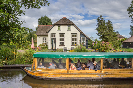 Tourists taking a tour in the canals of Giethoorn, Holland
