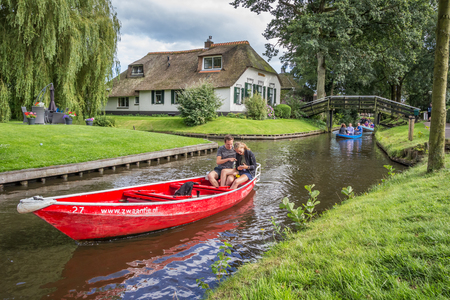 Tourists in an electric boat in the canals of Giethoorn, Holland
