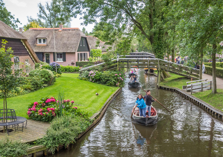 Tourists moving a traditional punter boat through the canals of Giethoorn, Holland Editorial