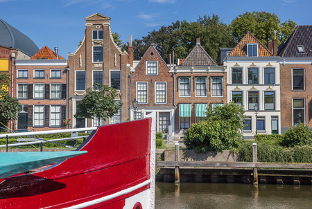 Bow of a red ship and historical houses in Zwolle, Netherlands