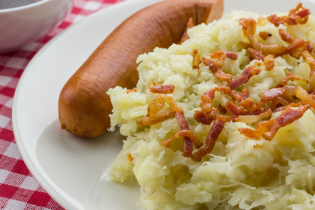 Typical dutch dish zuurkool with sauerkraut, bacon and smoked sausage on a traditional red and white tablecloth