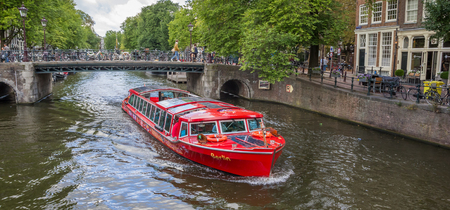 Tourboat with tourists during a sightseeing tour of the canals of Amsterdam, Holland