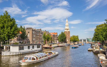 Tourist cruiseboat and historical tower in Amsterdam, Holland