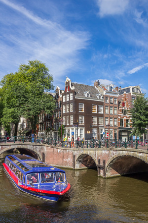 Tourist cruiseboat in the canals of historical Amsterdam, Holland