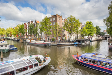 Two tourboats at a canal intersection in Amsterdam, Holland
