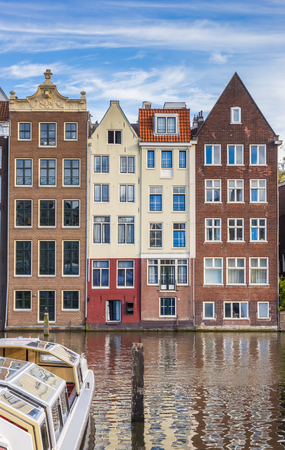 Traditional houses and a cruiseboat at the Damrak in Amsterdam, Holland