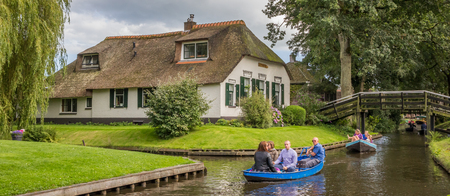 Panorama of tourists in an electric boat in the canals of Giethoorn, Holland