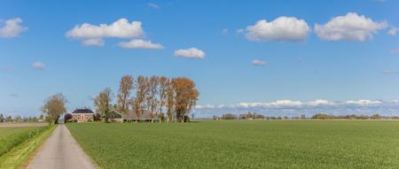 Narrow road leading to a farm in the dutch landscape near Groningen