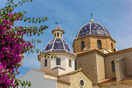 Pink flowers in front of the blue domes of the church in Altea, Spain Фото со стока
