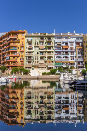 Colorful apartment buildings reflected in the water of Port Saplaya in Valencia, Spain