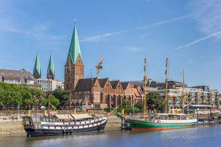 Historical ships and church along the river Weser in Bremen, Germany