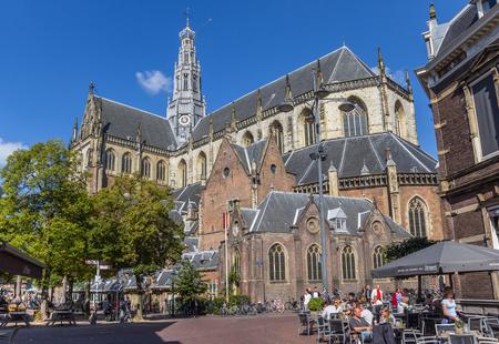 Mensen die van de zon genieten bij de St. Bavo-kerk in het centrum van Haarlem, Nederland