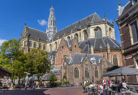 People enjoying the sun at the St. Bavo church in the center of Haarlem, Netherlands Editorial